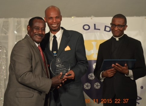 "Everald ""Gally"" Cummings is honoured as one of the first fifty inductees into the Fatima Old Boys Association (FOBA) Hall of Achievement @ the Induction Ceremony in November 2015. Presentation made by Dwight Andrews, President of (FOBA) accompanied by Fr. Gregory Augustine, Principal of Fatima College."