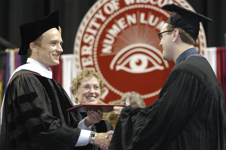 Actor and Madison native Bradley Whitford distributes diplomas to graduates after speaking at a UW-Madison Commencement ceremony.