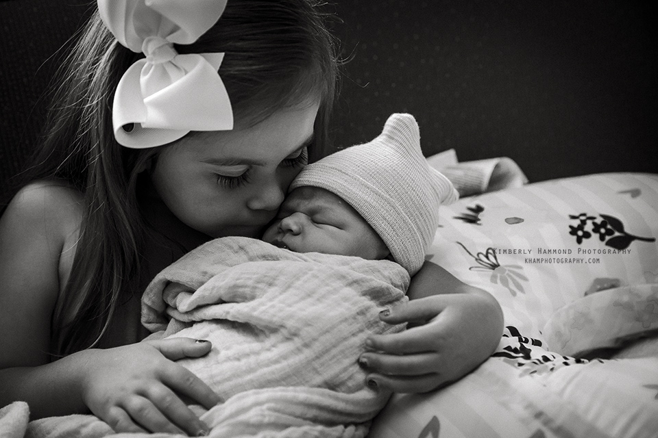 Big sister snuggles with her brand new baby sister at Mansfield Methodist in Mansfield, TX.