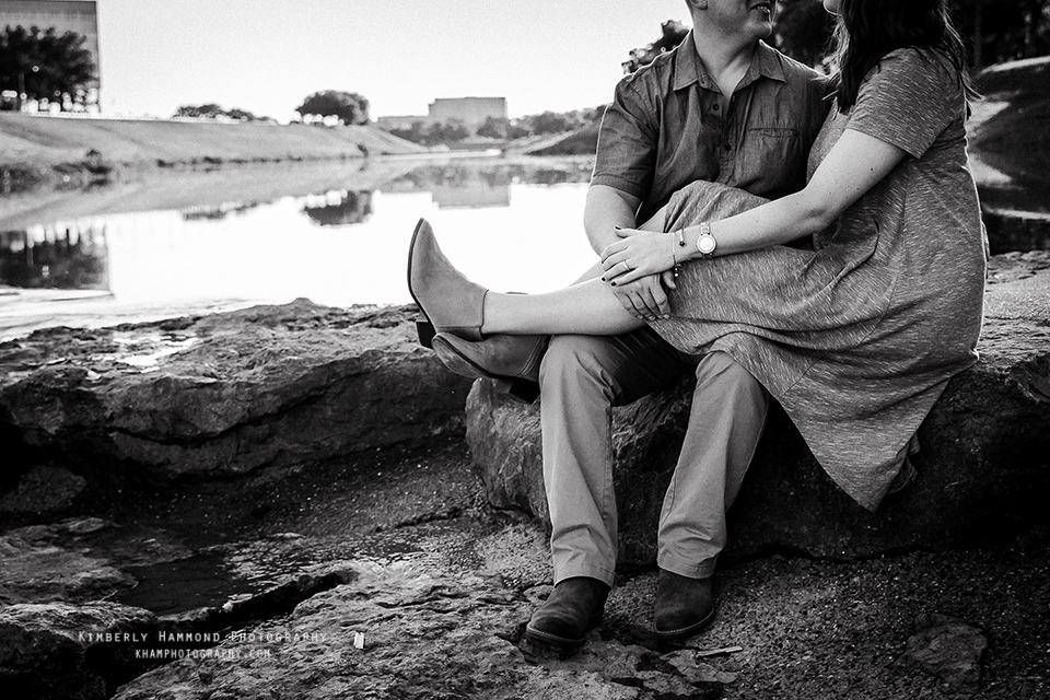 Man and woman sit together during their engagement photography session at Trinity Park in Fort Worth, TX.