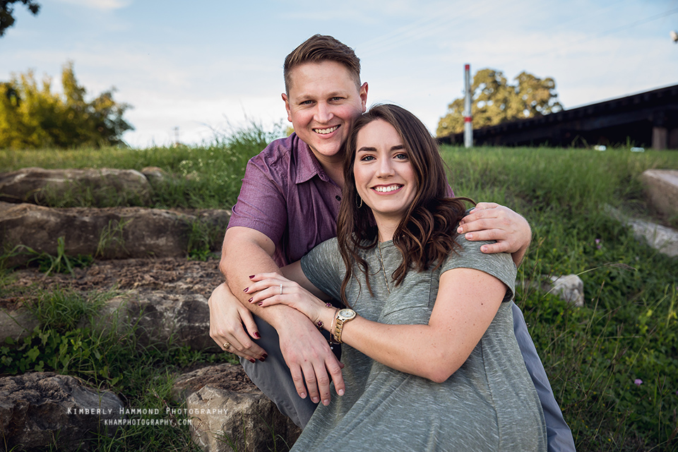 Man and woman sit on the bank of the Trinity River during their engagement photography session at Trinity Park in Fort Worth, TX.
