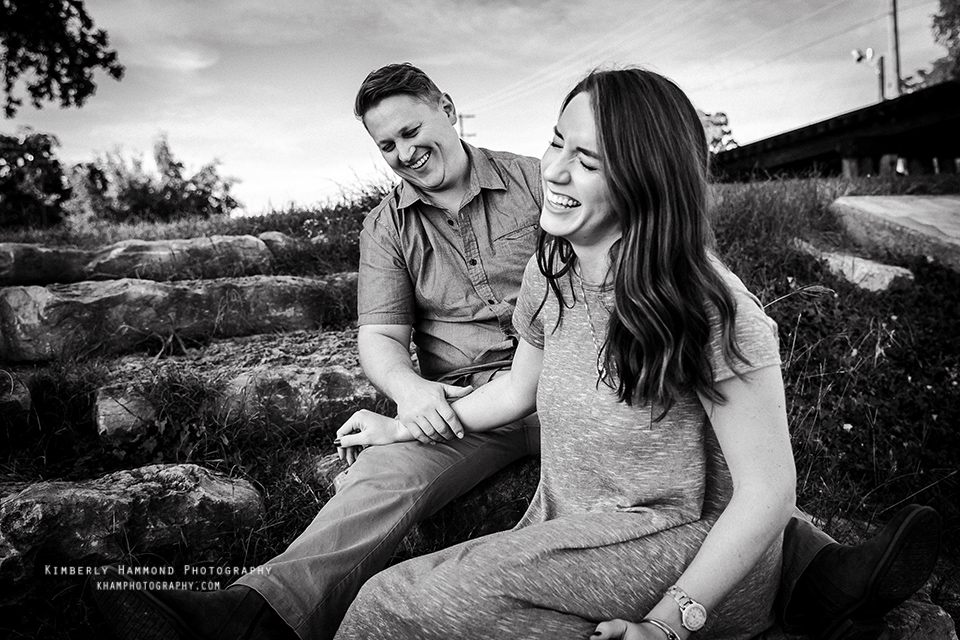 Man and woman sit together and laugh during their engagement photography session at Trinity Park in Fort Worth, TX.