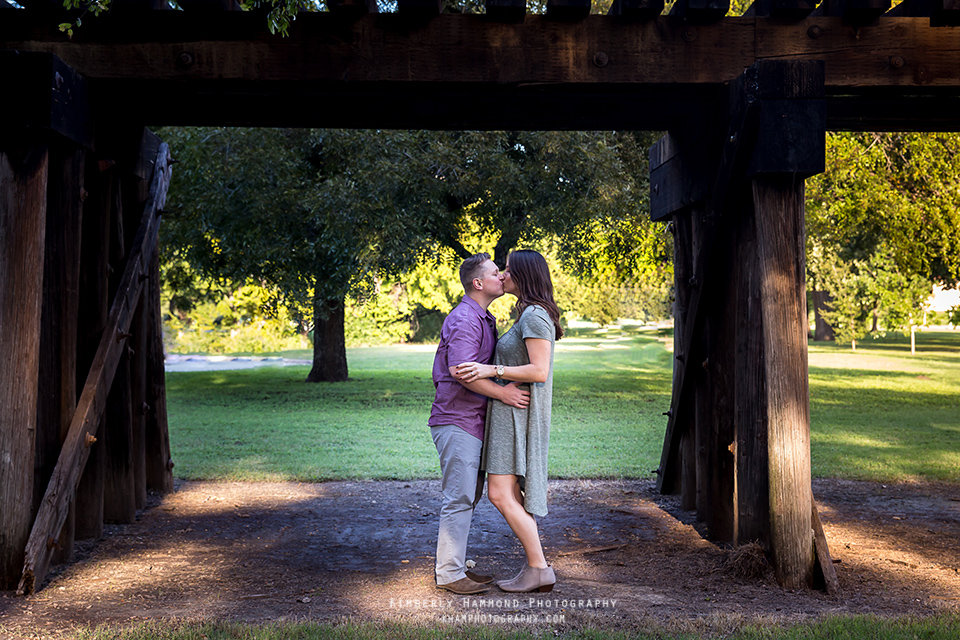 Man and woman kiss under a bridge during their engagement photography session at Trinity Park in Fort Worth, TX.