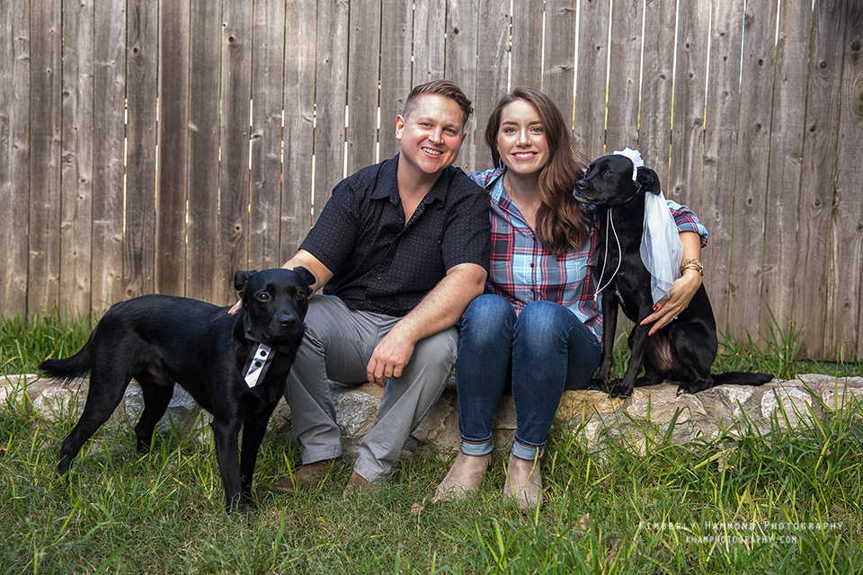 Man and woman poses with their dogs during their engagement photography session at Trinity Park in Fort Worth, TX.