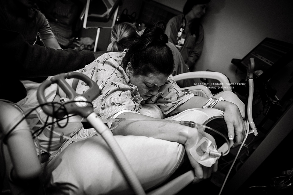 Mom tries hands and knees while laboring with her VBAC baby at Harris Methodist in Downtown Fort Worth TX.