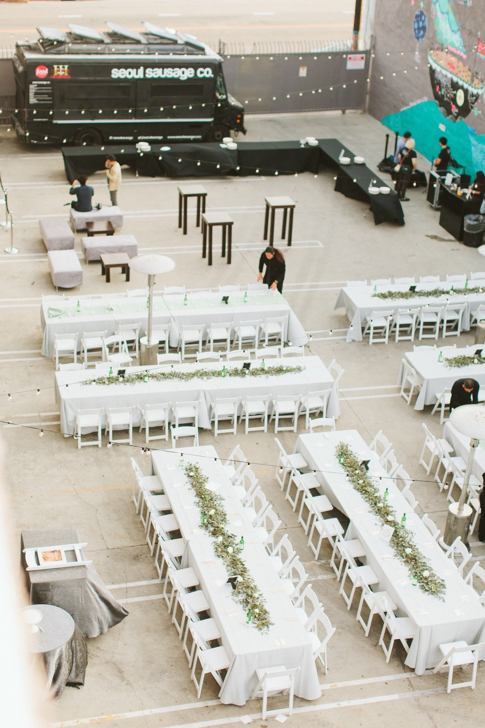 Outdoor space was transformed from a parking lot, to an amazing space with long tables, eucalyptus leaves, a clean, white settings.