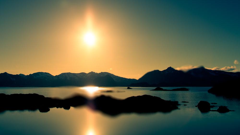 """Kaukaisten ja muuntuvien asioiden  kuten auringon, veden väreilyn tai valon heijastusten kuvaileminen on haastavaa. Valokuvataiteilija Dinah Junkerin kuva """"Panorama X"""" on kuvattu Lofooteilla. Kuvan kuvailutulkkaus tekstissä alla."""