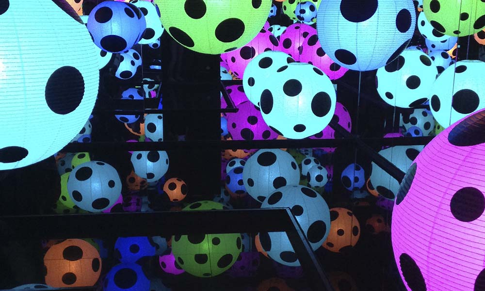 """Yayoi Kusaman installaat  ion  """"Elämän hymni"""" sisällä hahmotuskyky hämärtyy. Pimeä peilihuone vaikuttaa yhtä aikaa ahtaalta ja äärettömän avaralta. Kaikki pinnat ovat peilaavia ja katosta roikkuu suuria, pallomaisia paperivalaisimia, joiden sisällä hehkuu erivärisiä valoja. Lisätietoa projektista ja teoksen kuvailutulkkaus alla."""