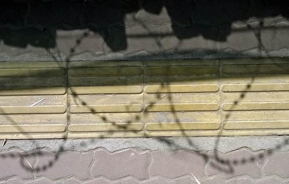 Näkövammaisten asema on Nepalissa heikko.  Kuvassa on keltainen, kohoraitainen opastenauha laatoitetulla jalkakäytävällä. Vaakasuuntaisen opasteraidan päälle lankeaa dramaattinen musta heittovarjo muurin laella kiemurtelevasta piikkilankaesteestä.
