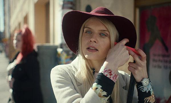 Kuvassa lierihattuinen Donna (näyttelijä Alina Tomnikov) painaa puhelimen korvaansa vasten ja näppäilee sitä. Kuva: Production House.