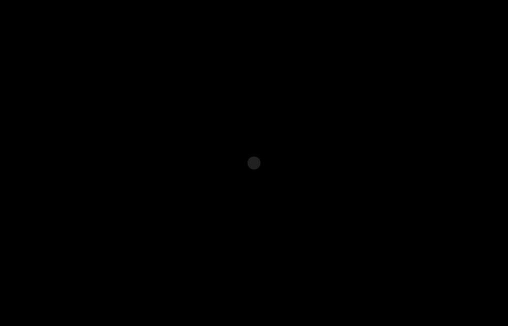 Kuvassa on täydellisen sysimusta väripinta, jonka keskellä on hädin tuskin erotettavissa oleva lähes musta piste.