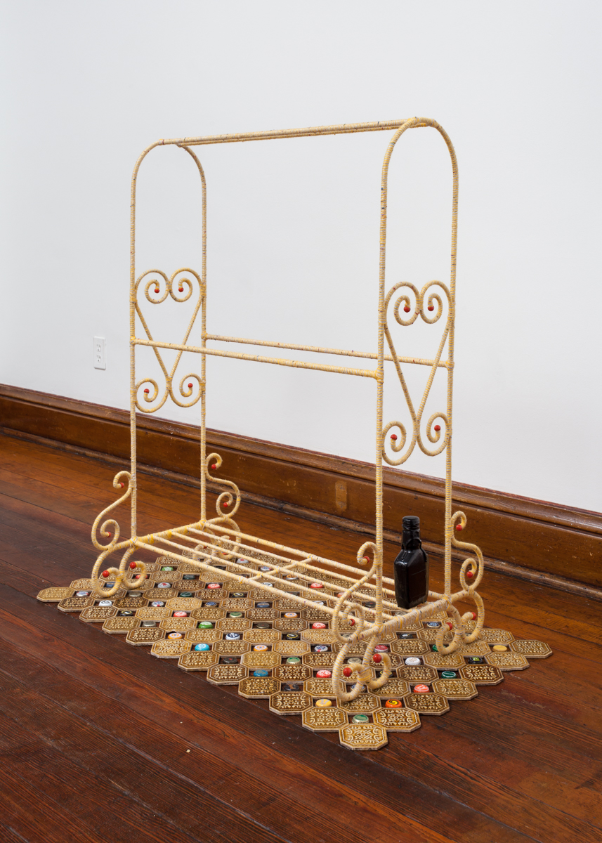 "Guilt Rack  42"" x 38"" x 13"", wire frame quilt rack, yarns, One Shot enamel, bottle of Maker's Mark, tiles, and beer bottle caps, 2015"