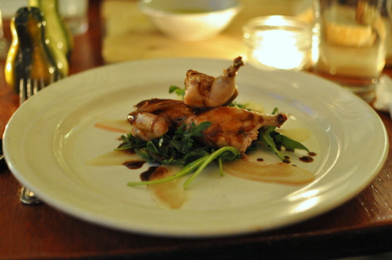 Honey-glazed quail on a bed of greens, pears, and chocolate.