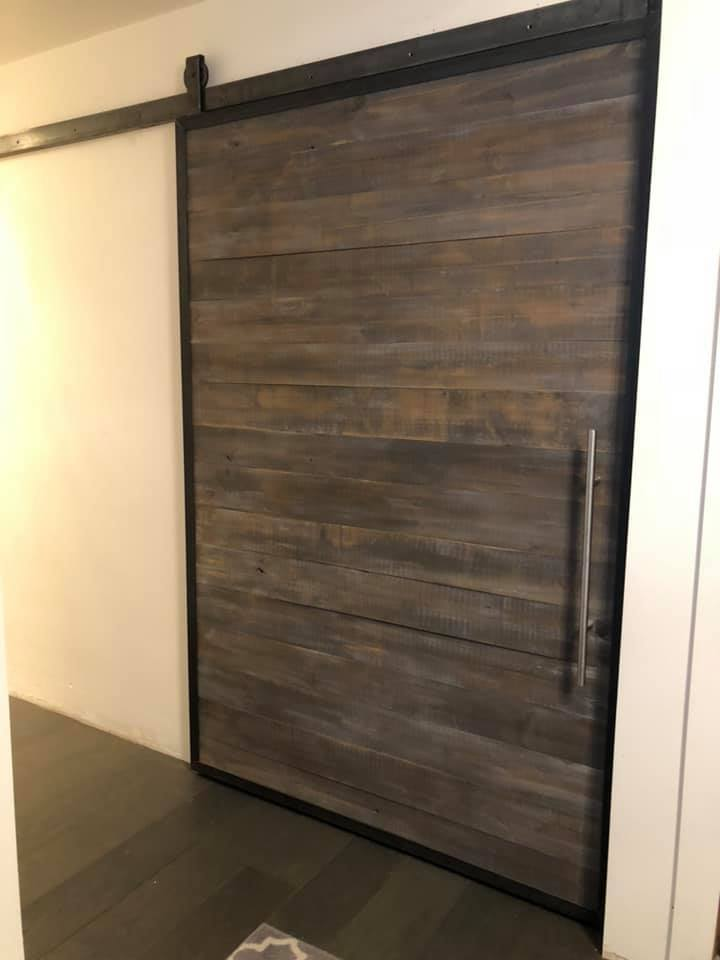 Sleek barn doors to cover closet openings to keep a clean de-cluttered look in the bedroom.