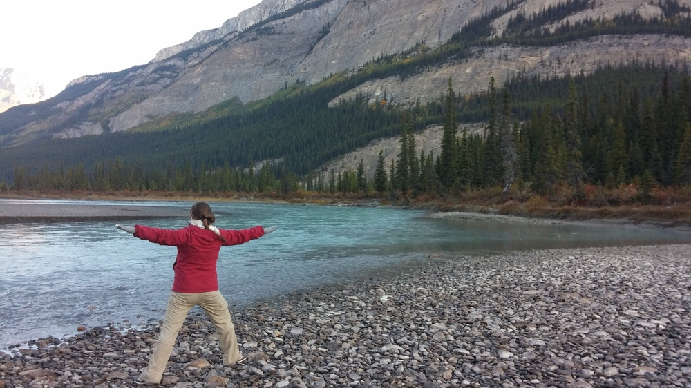 Morning yoga along a river in Banff National Park, Alberta.