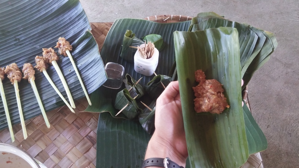 Rolling the pork in banana leaves.