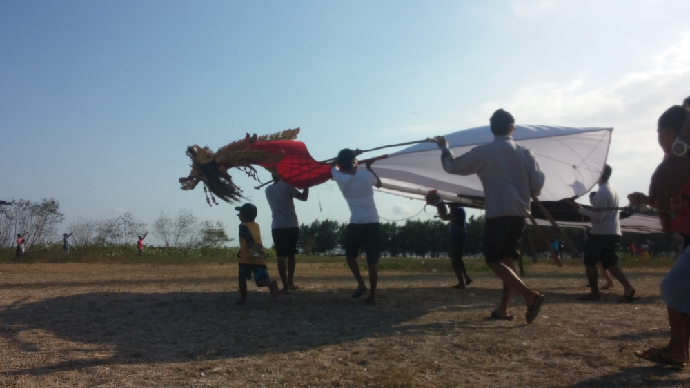 A team bringing in a kite to launch! Check the dragon face!