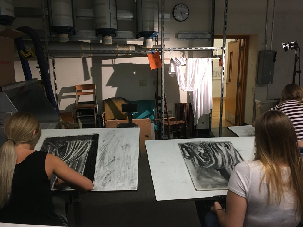 Students drawi draped fabric with charcoal using a reductive/subtractive method.