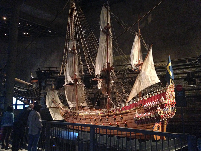 "A ""miniature"" replica of the ship (actual ship shown behind it)."