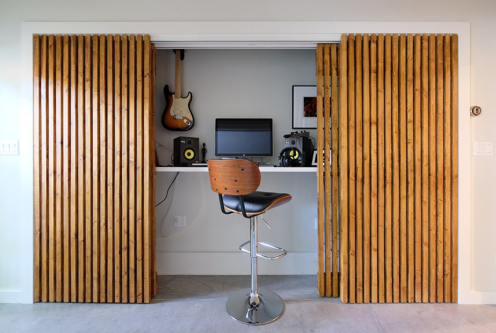 hidden music closet with custom wood sliding doors.jpg