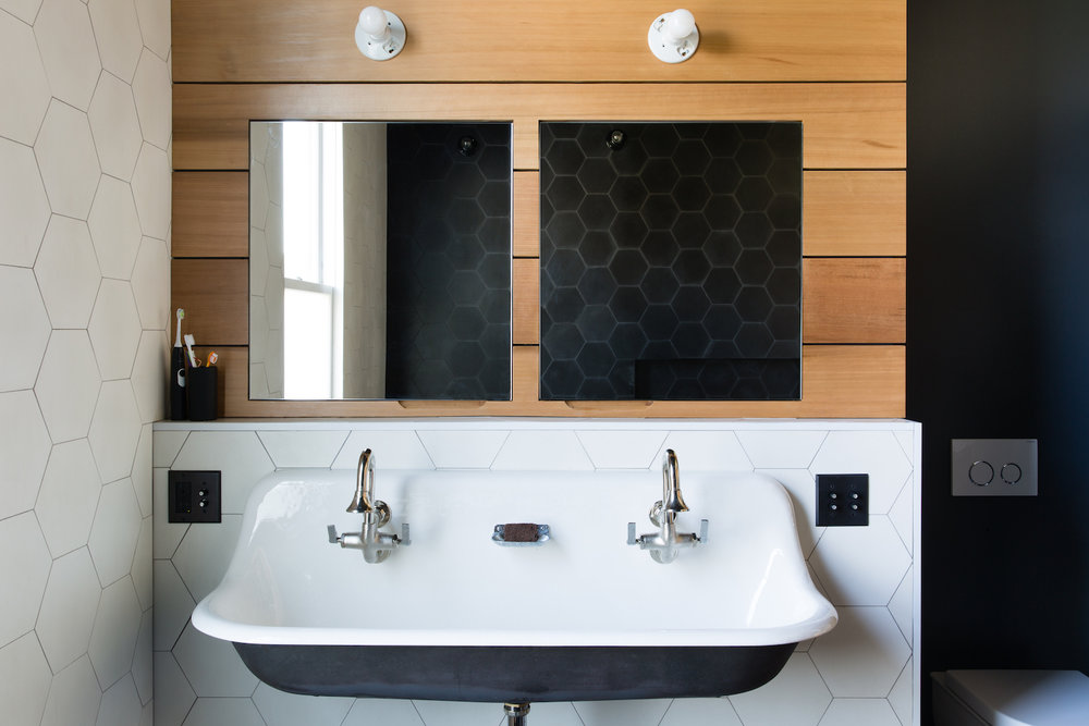 bathroom with white tile walls and accent wood paneling and white trough sink and chrome fixtures.jpg