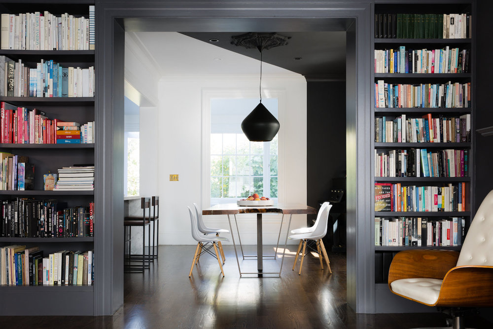 black built in bookshelves and dining area with wood dining table and white dining chairs and black pendant light.jpg