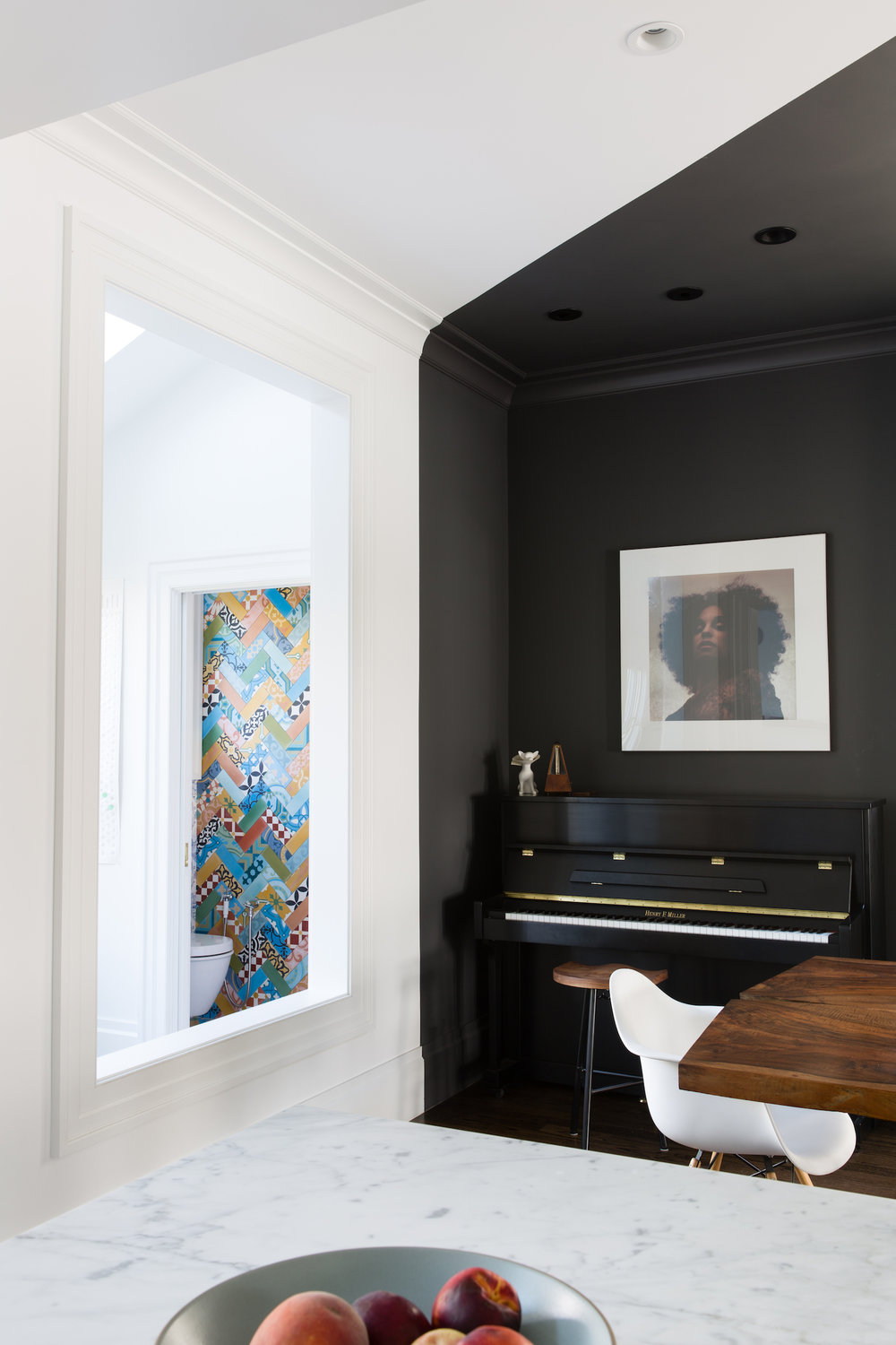 dining area with black and white walls and ceiling and black piano and live edge wood table and white dining chair.jpg