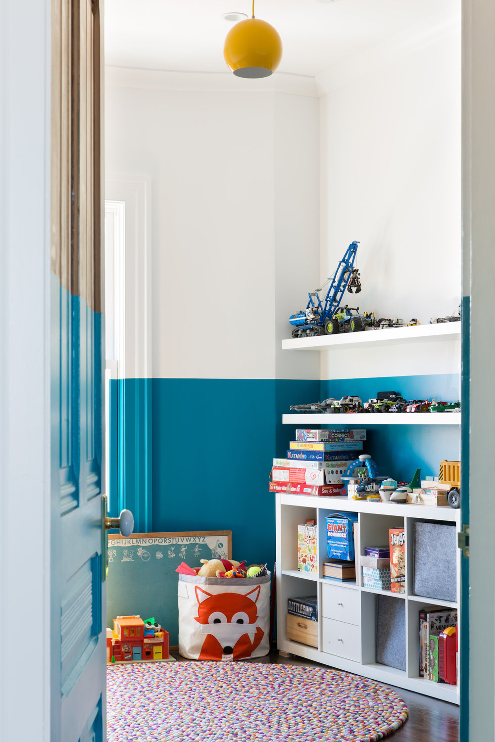 kids room with white and blue walls and white storage shelving and mulicolor rug.jpg