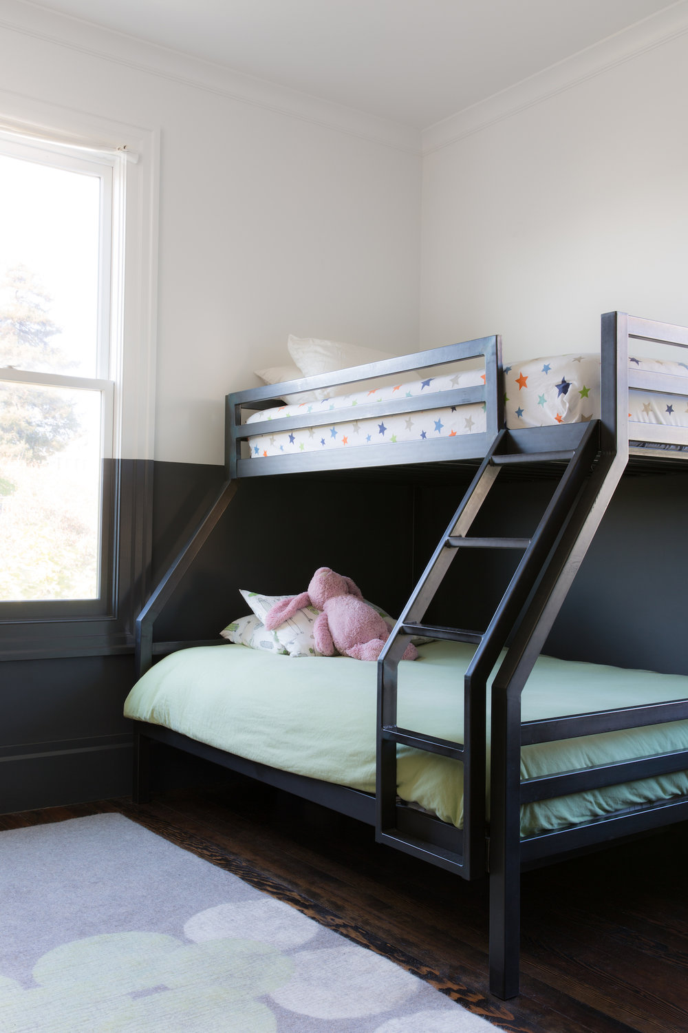 kids room with bunk beds and black and white walls and purple rug and wood flooring.jpg