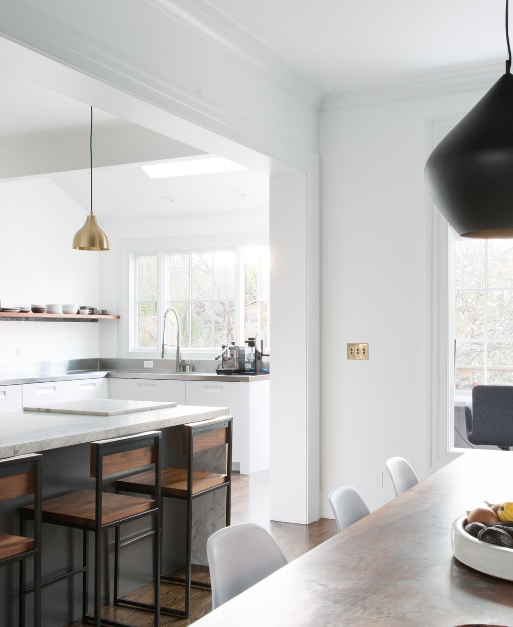 kitchen and dining area with bar seating and live edge dining table and white dining chairs and marble island counters and steel kitchen counters and white cabinets and open shelving and gold pendant light.jpg