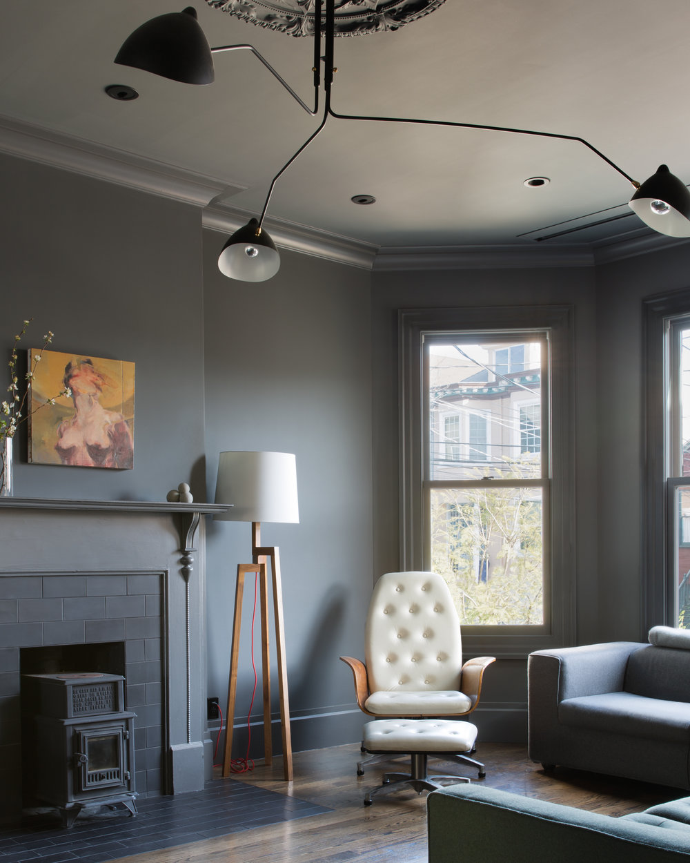 living area with black walls and ceiling and black light fixtures and grey and white furniture.jpg