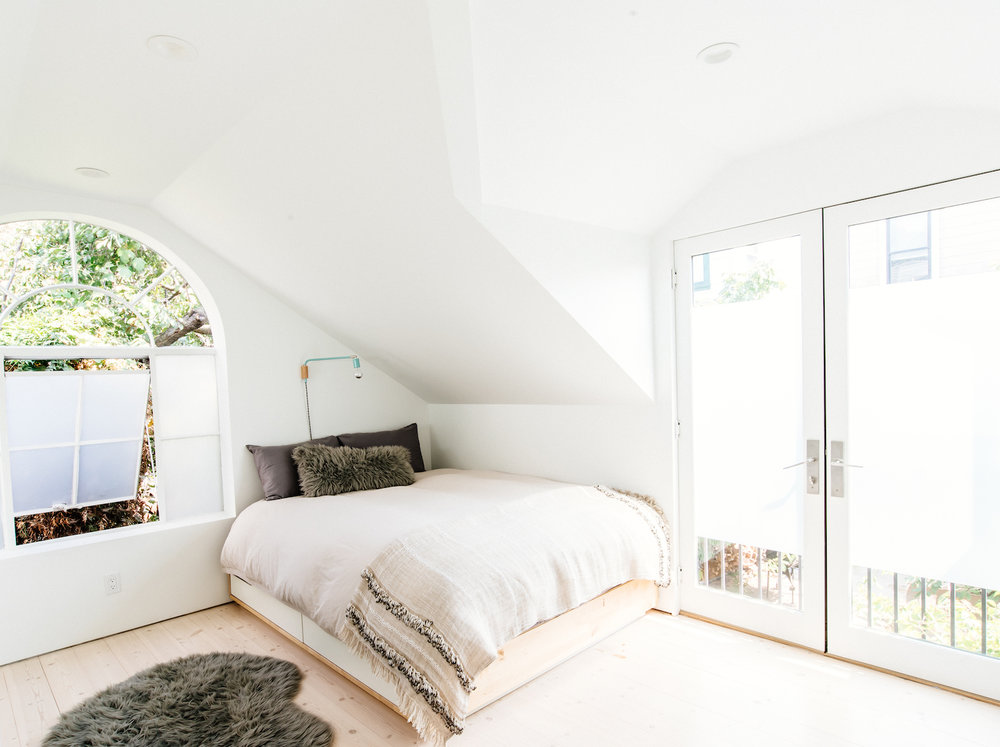cottage bedroom with white walls and white balcony doors and wood flooring and grey accent rug.jpg