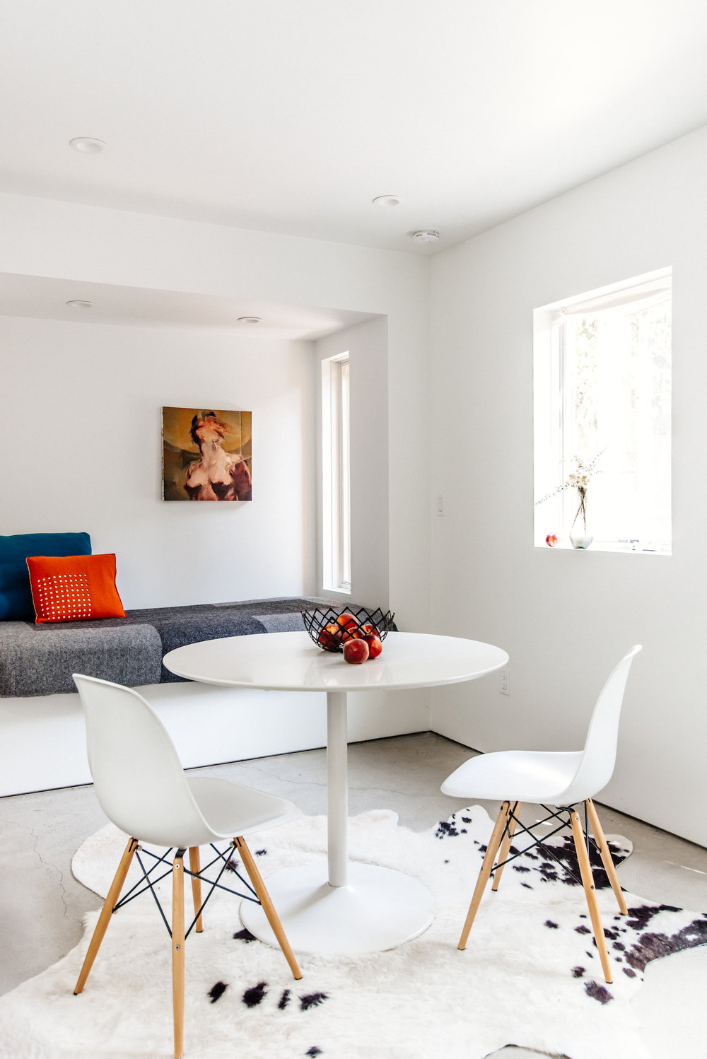 dining area with white table and built in seating area with grey cushion and cowhide rug and stained cement floors.jpg