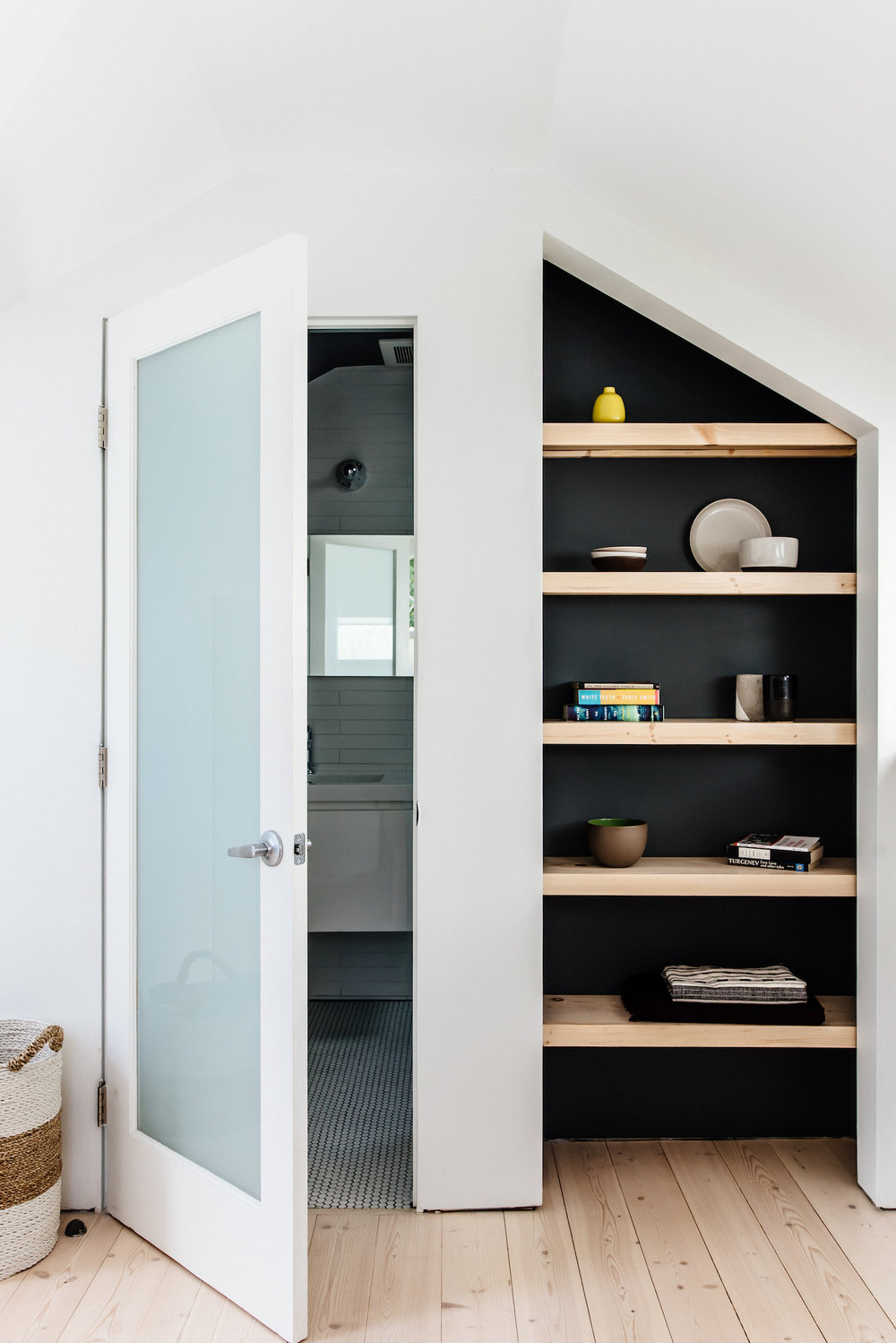hallway with custom built in shelving and wood flooring and bathroom entry with white glass door.jpg