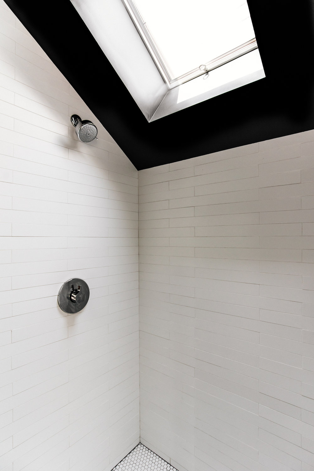 shower with white tile and skylight and chrome shower fixtures.jpg