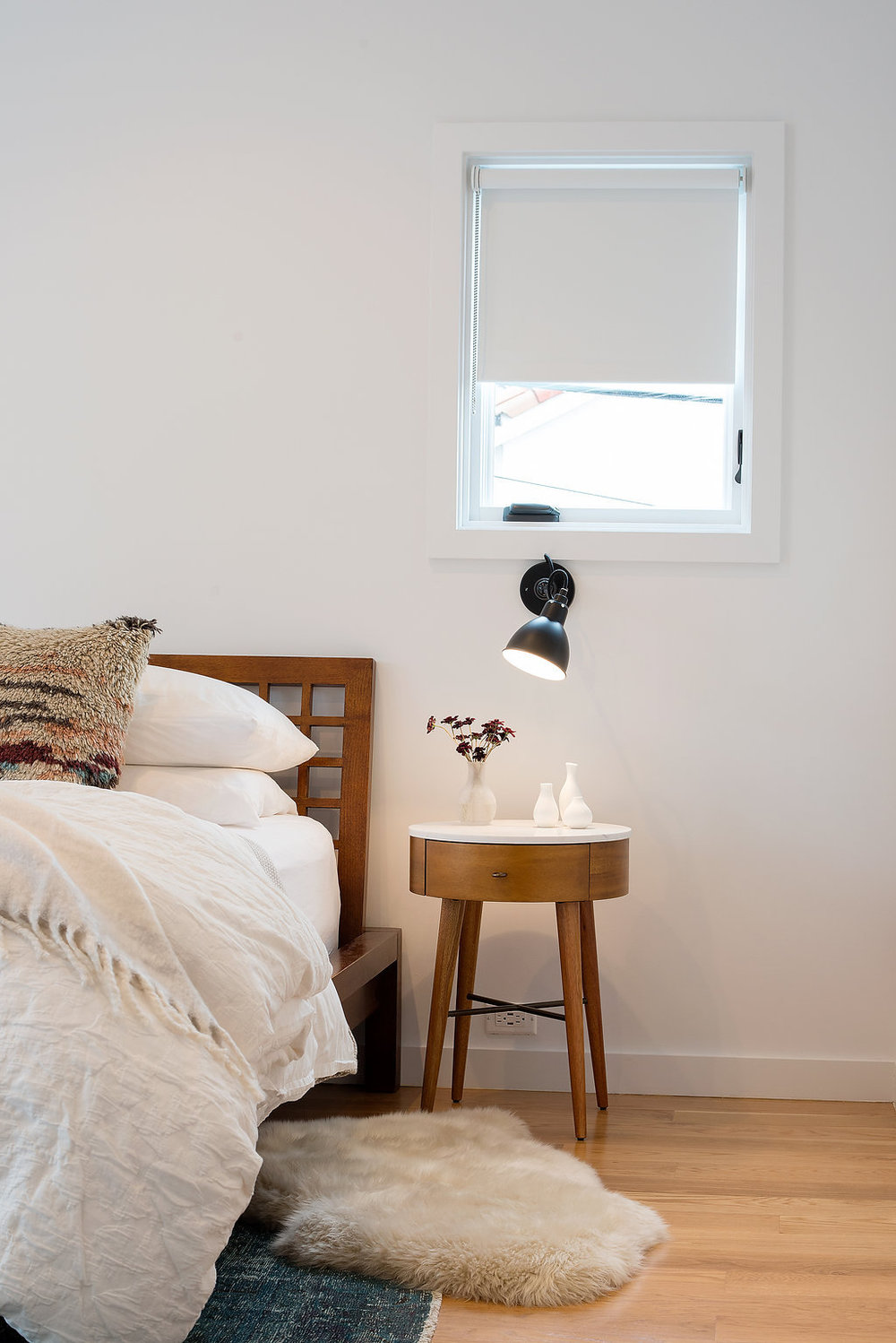 bedroom with wooden bed and black wall lamp and wood nightstand and sheepskin rug and wood flooring.jpg