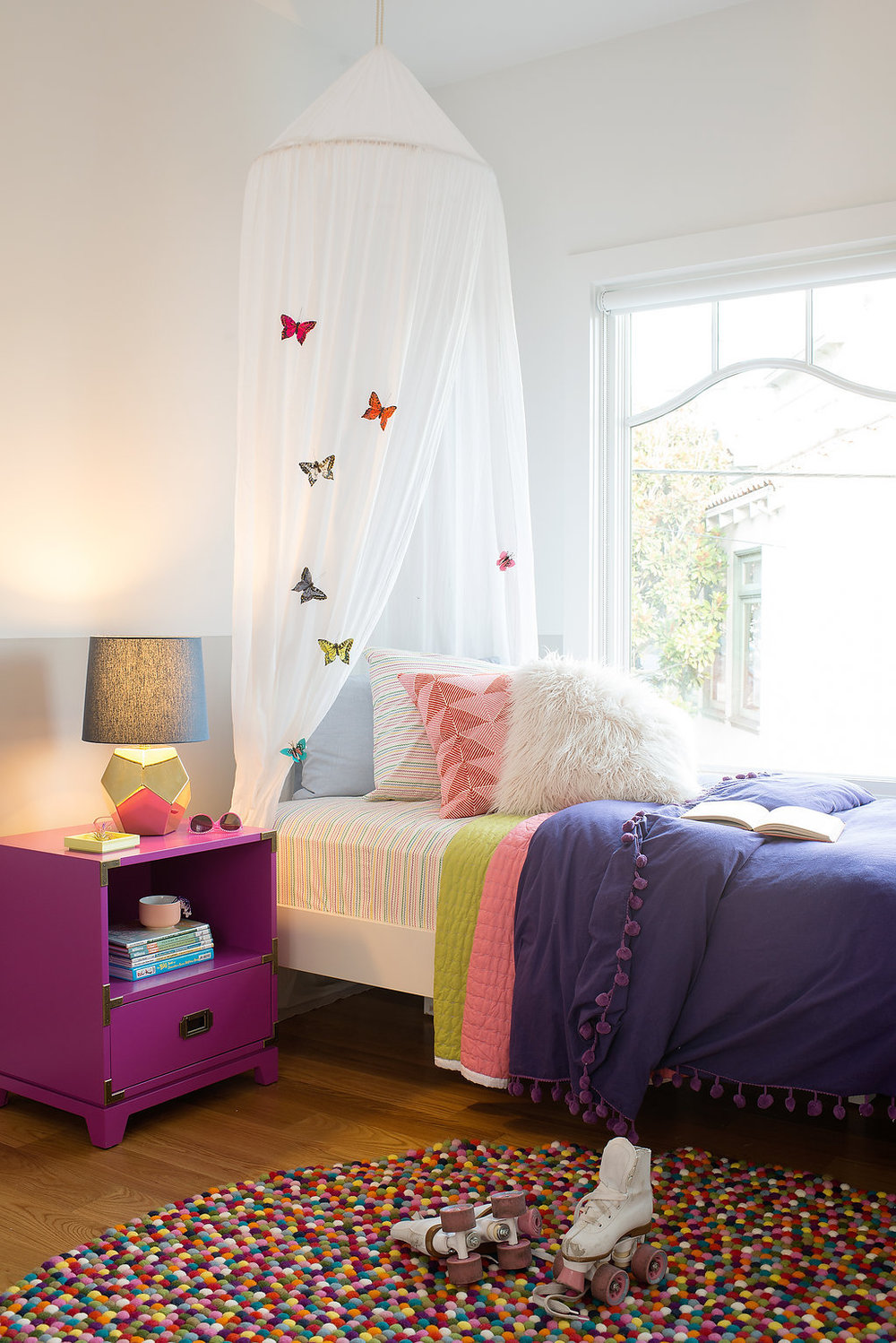 kids bedroom with colorful dotted rug and bed with butterfly canopy and pink nightstand and gold lamp.jpg