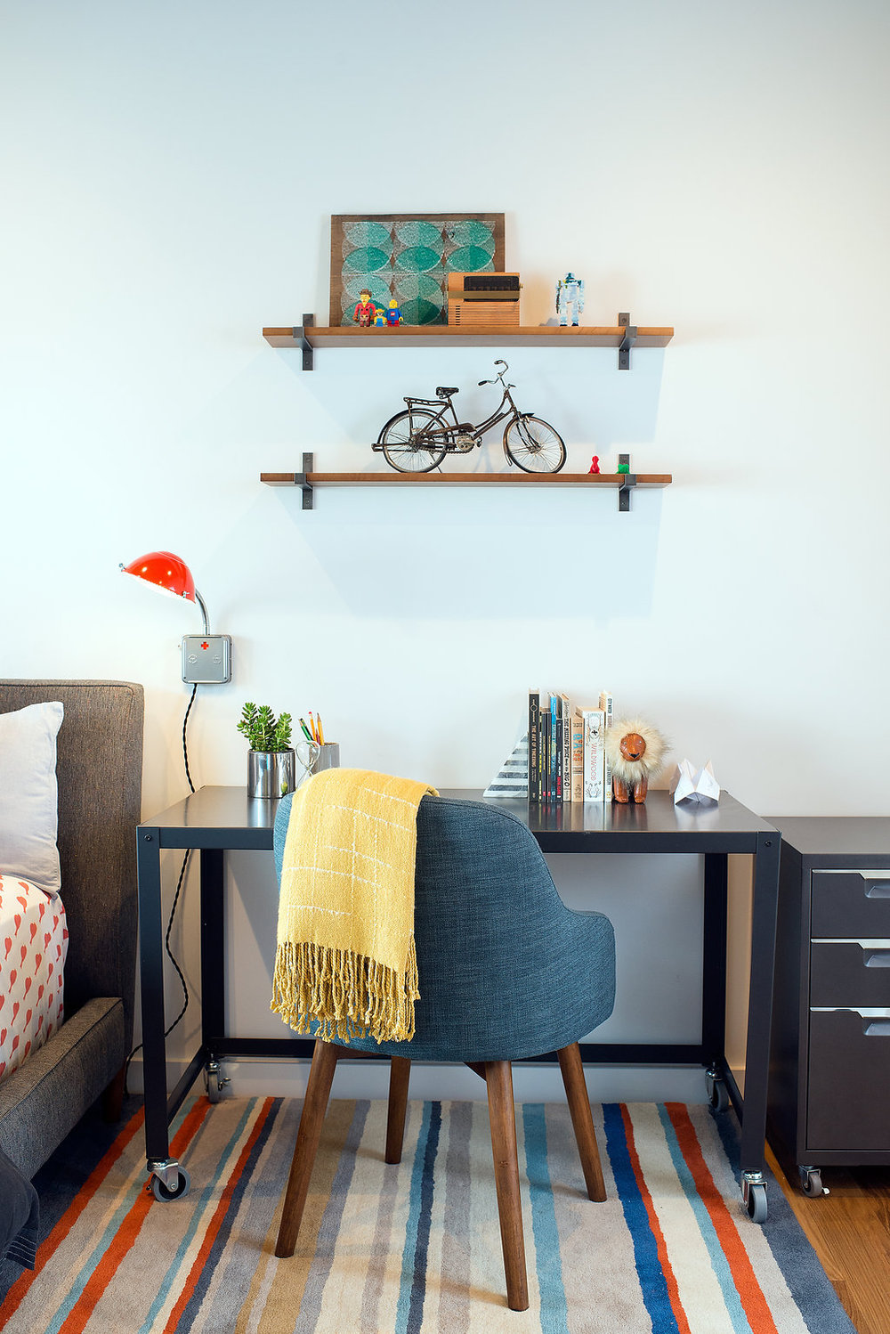 kids desk area with rolling desk and blue accent chair and bright accessories.jpg
