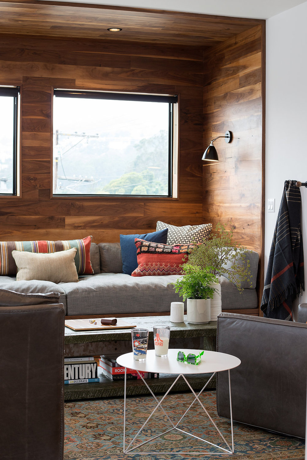 living area with custom built in seating and leather accent chair and white accent table.jpg