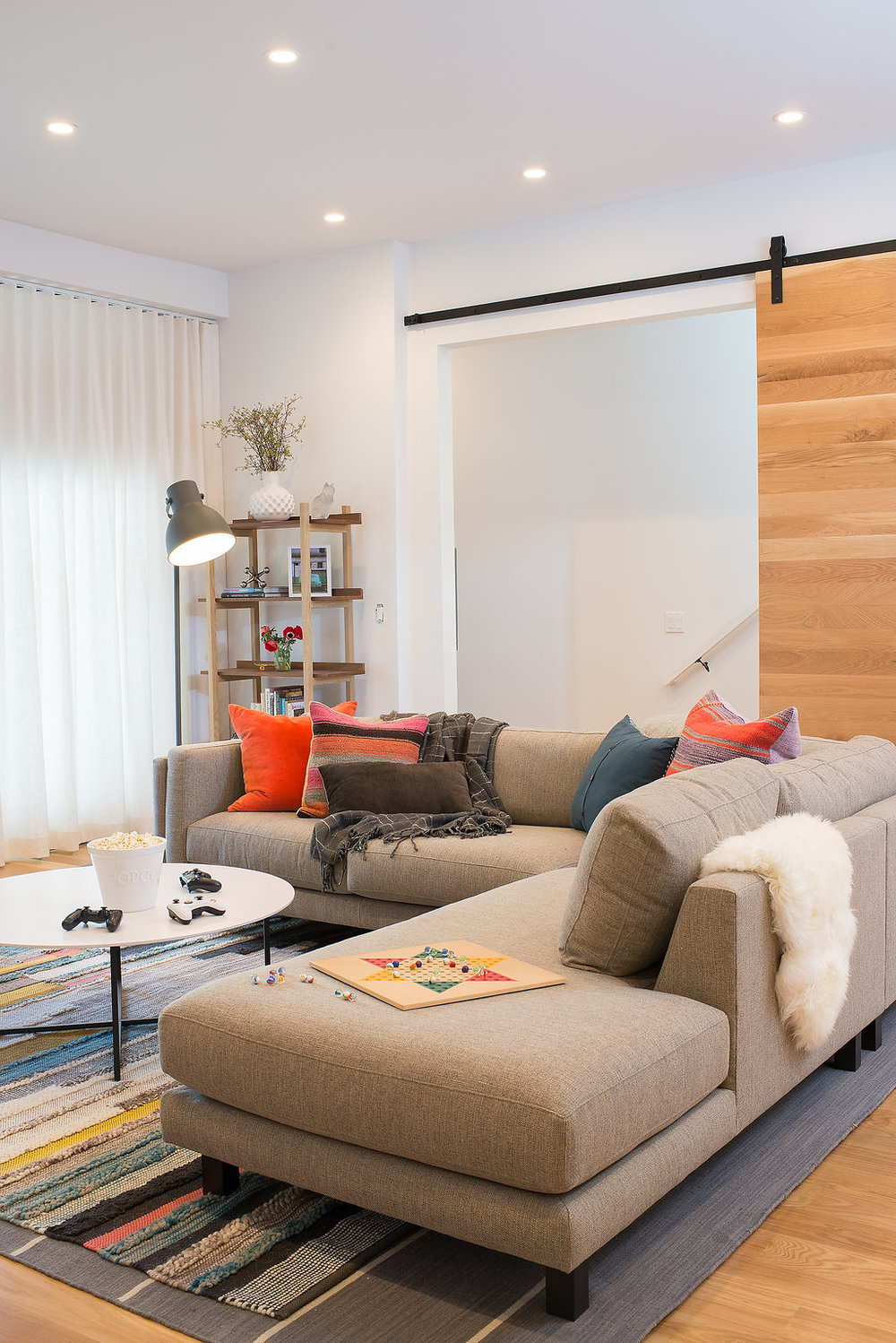 living area with wooden barn door and grey sofa and layered rug and white coffee table.jpg
