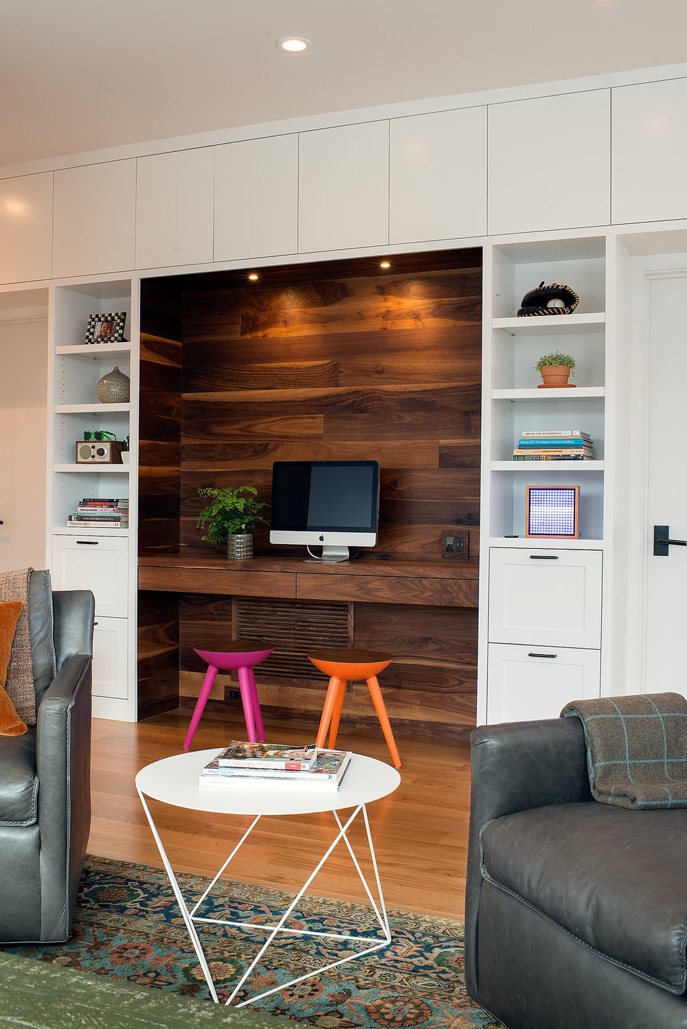 custom wood built in desk area with open shelving and drawers and colorful accent chairs.jpg