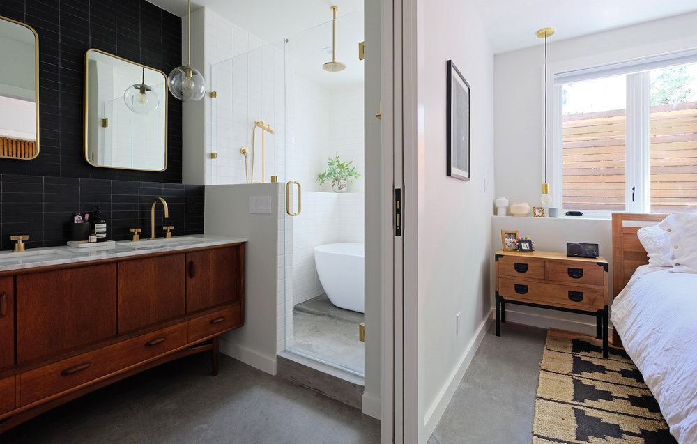modern black and white bathroom with brass fixtures and wooden vanity and cement floors.jpg