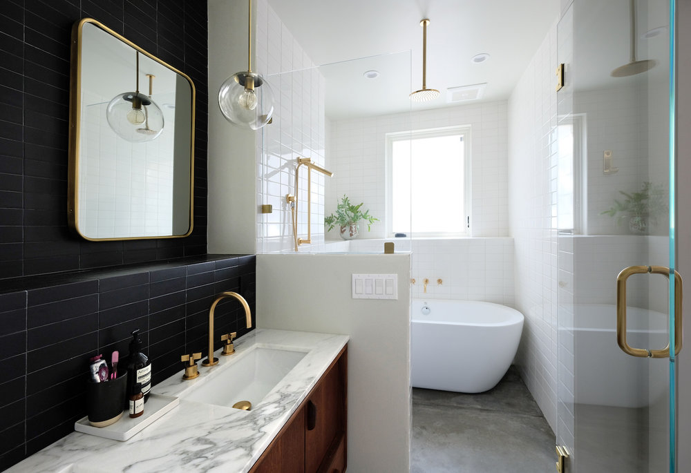 modern black and white bathroom with brass fixtures and walk in shower and freestanding tub and wooden vanity and cement floors.jpg