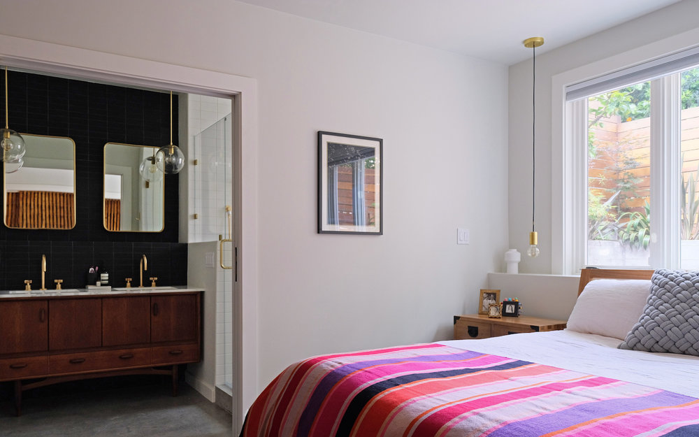 master suite with cement floors and brass fixtures and striped bedding.jpg