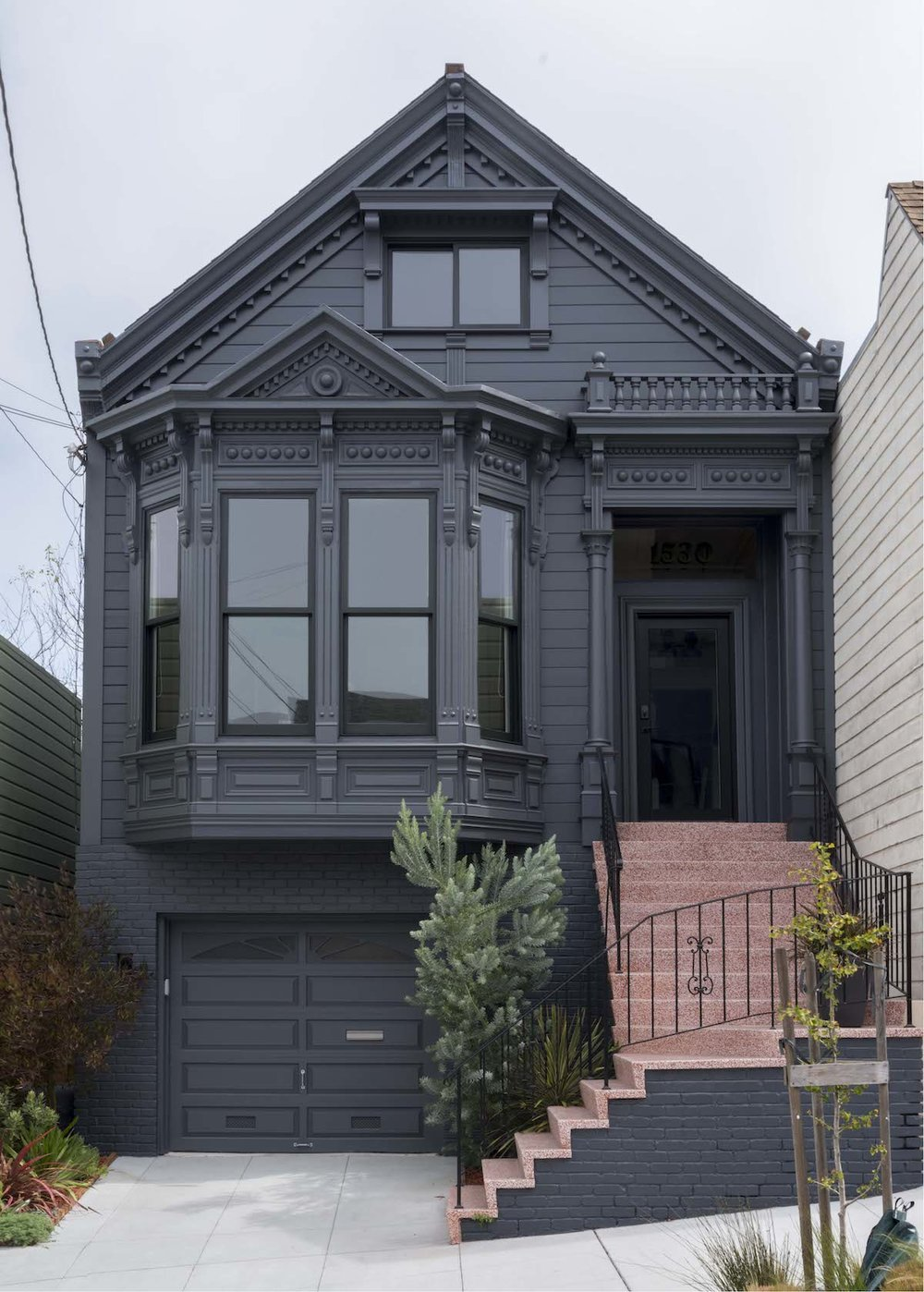 black exterior with black trim windows and door and red staircase with black railing.jpg