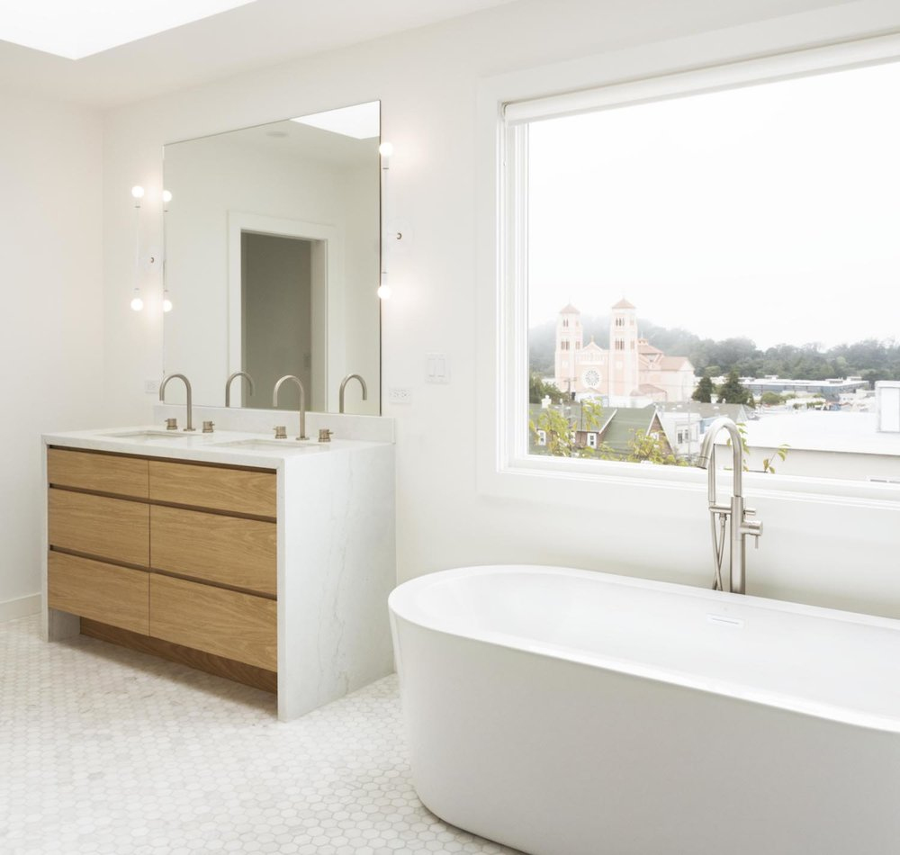 white bathroom with marble hexagonal floor tile and freestanding tub and brushed nickel hardware and custom wood vanity with waterfall counter.jpg