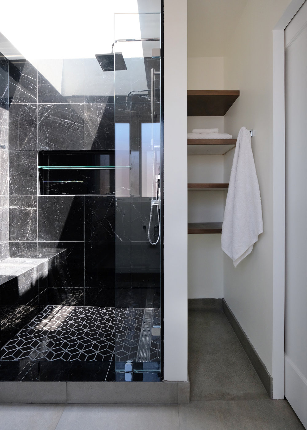 black marble tile shower with bench and chrome fixtures and storage area with custom shelving.jpg