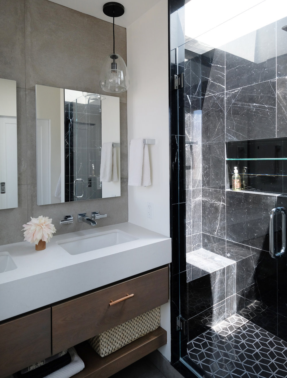 custom wood floating vanity with double sinks and mirrors and black marble tile shower and mosaic flooring.jpg