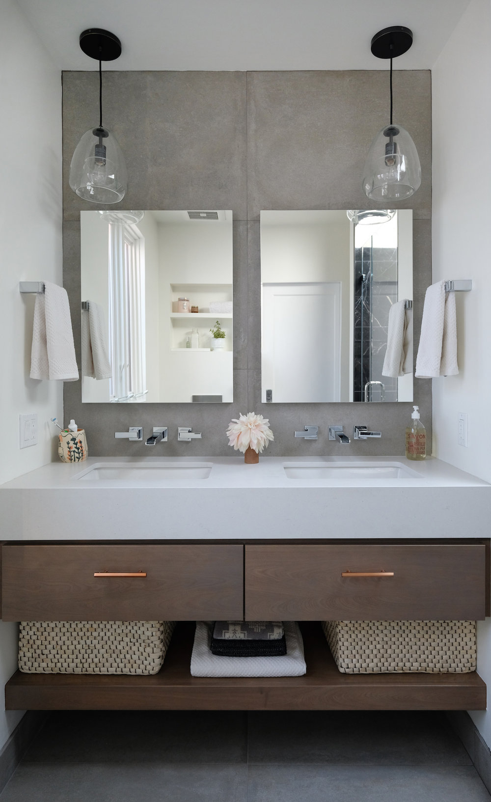 custom wood floating vanity with undermount sinks and wall mounted faucets and pendant lighting.jpg