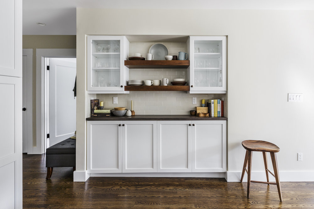 kitchen storage area with white glass front cabinets and open wood shelving.jpg